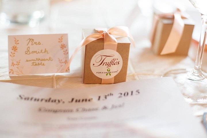 Petal peach ribbon on singe piece kraft favor box with chocolate caramel twist truffles at a single table setting.