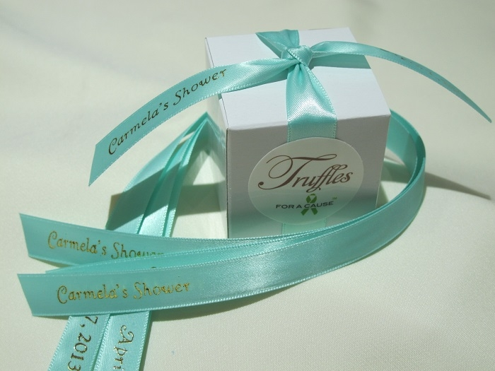 Aqua ribbons on white boxes for a baby shower with chocolate mini truufles inside.