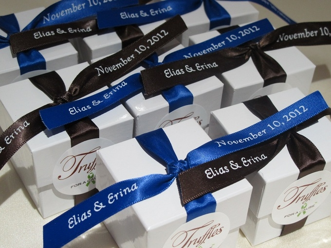 Brown & Royal Blue ribbons on white boxes with raspberry chocolate foil truffles inside.
