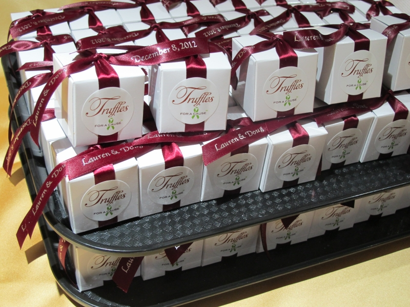 Burgundy ribbons on white boxes (in assembly), with dark chocolate truffles inside.