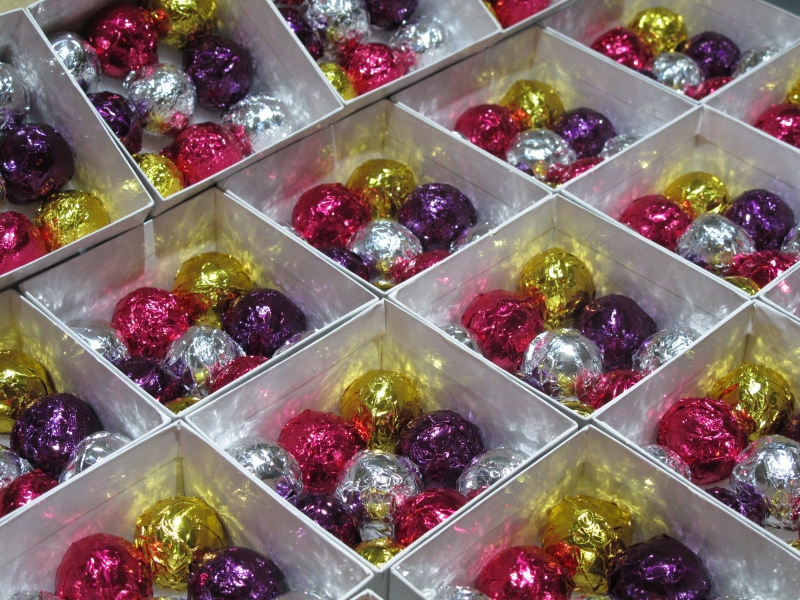 Deluxe Foil Production with 9 asssorted chocolate foil truffles visable in each favor box.