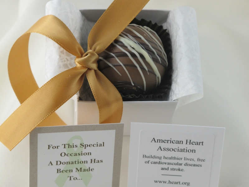 Gold ribbon with open Dessert Favor displaying caramel chocolate dessert truffle in box.