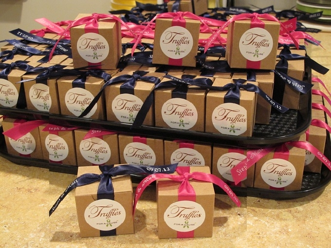 Navy & azelea ribbons on kraft  favor boxes on assembly trays with chocolate raspberry and amaretto truffles inside.