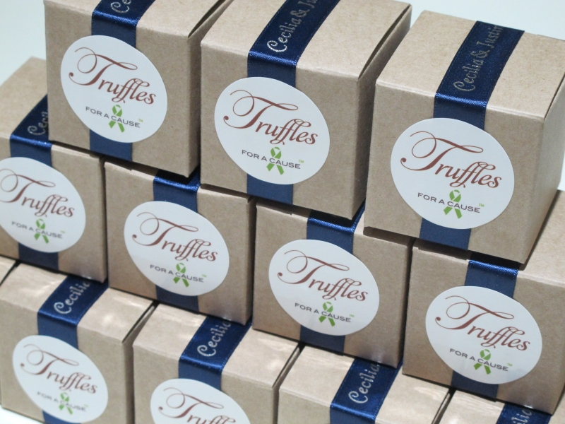 Navy ribbons on kraft favor boxes in assembly group with milk chocolate & dark chocolate truffles.