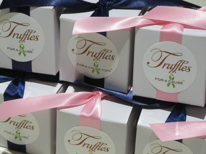 Close up of navy & pink ribbons on white one piece favor boxes with chocolate amaretto truffles inside.
