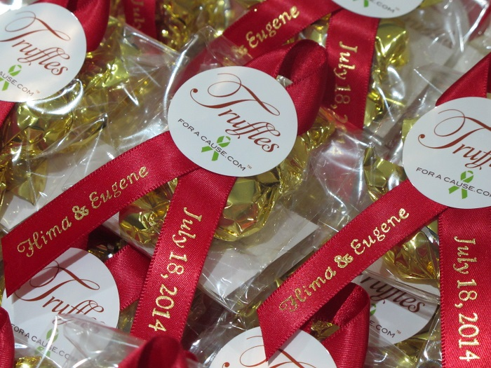 Close up of scarlet ribbons with gold mini truffles in Mini favors - chocolate wedding favors for Habitat for Humanity.