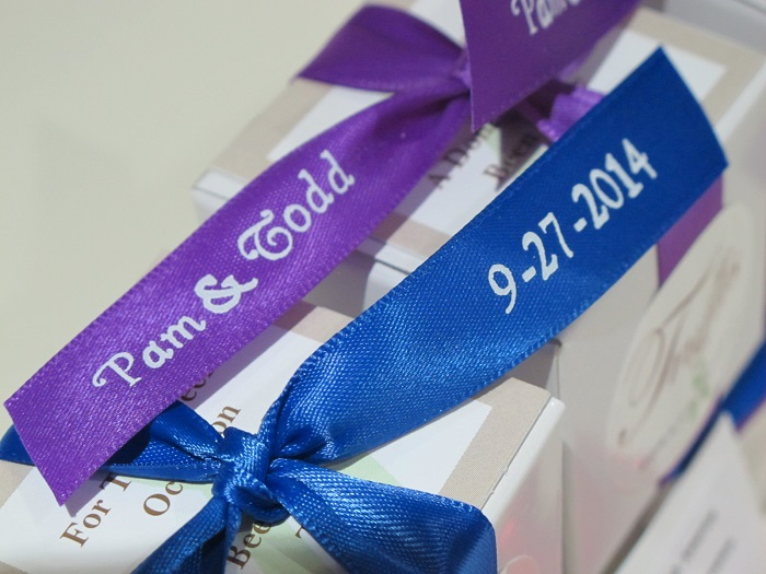 Close up view of printed royal blue & purple ribbons for Pam & Todd's chocolate wedding favors and charity donations.