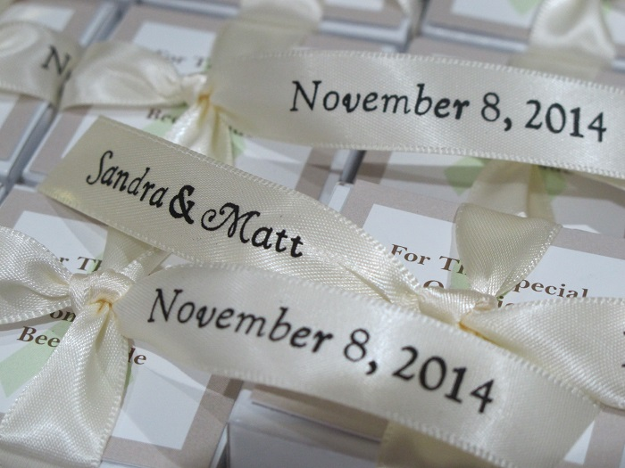 Philabundance wedding donation of close up of printed ribbons for Sandra & Matt tied on white favor boxes.