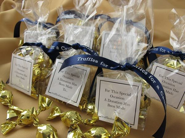 Cello favors - close up of navy ribbons tied on cello wedding favors with gold mini truffles inside.