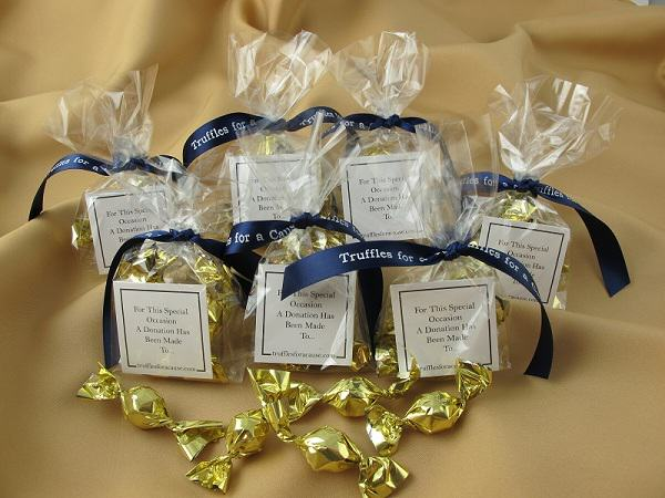 Cello favors with navy blue ribbons tied on cello twist wedding favors with gold mini truffles inside.