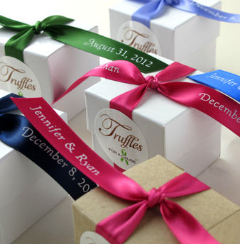 Overhead view of assorted ribbons & favor boxes with chocolate wedding favors inside.