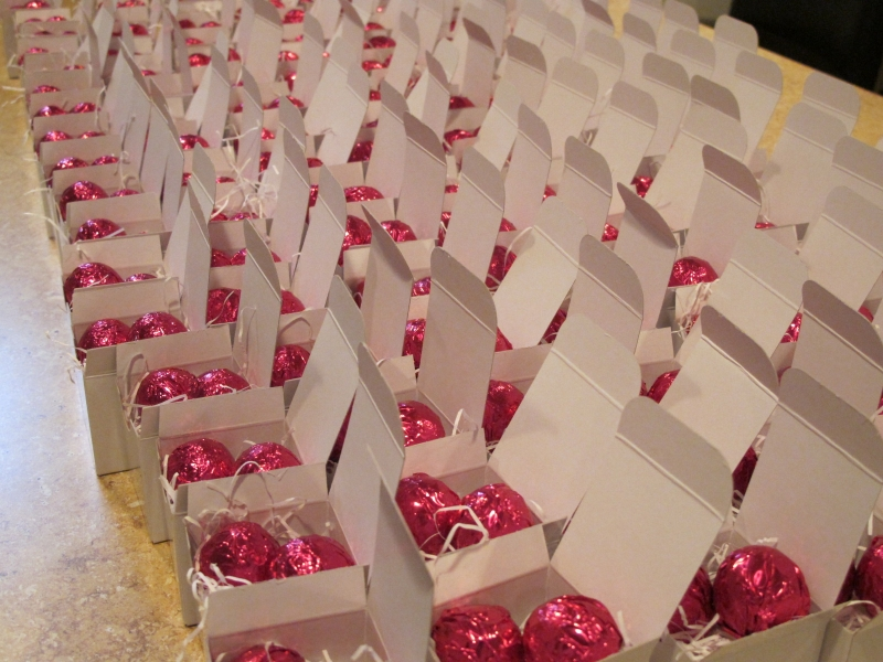 Assembly view of dark chocolate raspberry foil favors in white boxes.