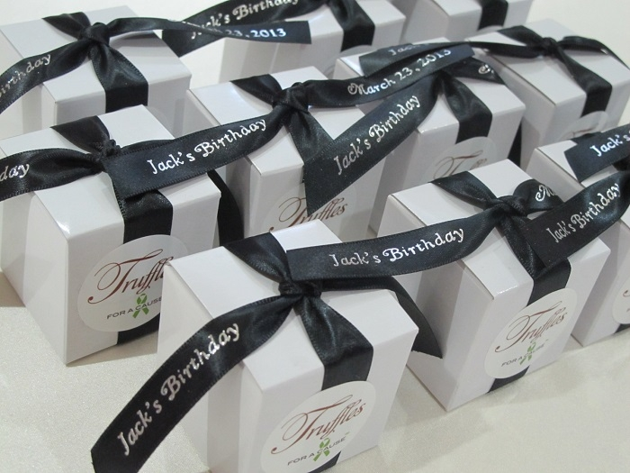 Black ribbons on white boxes with caramel chocolate truffles inside.