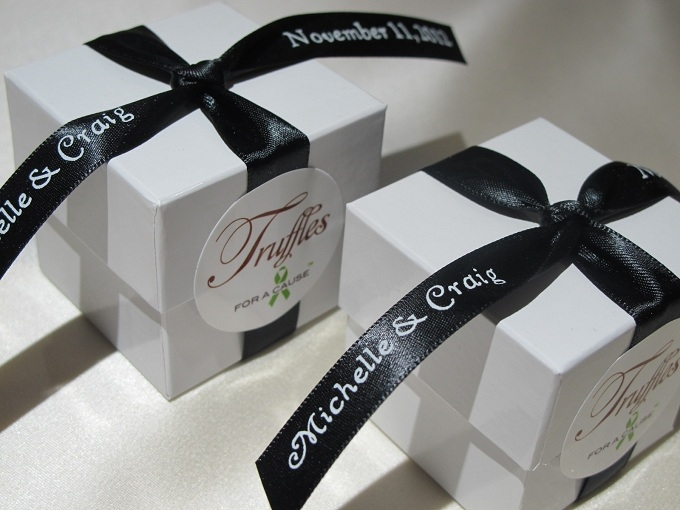 Black ribbons on white boxes with chocolate raspberry tuffles inside.