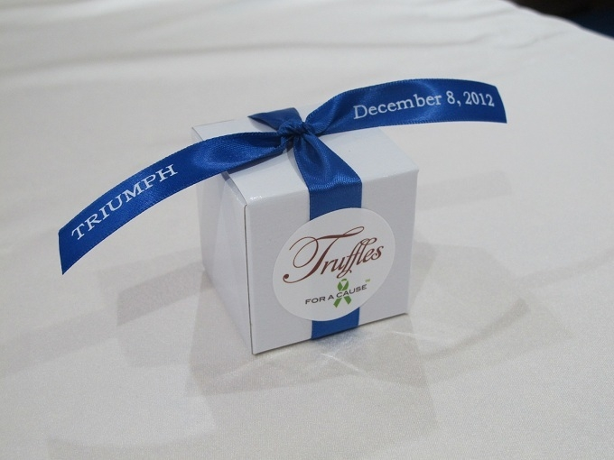 "Royal blue ribbons printed with corporate name of ""Triumph"" on white boxes with chocolate mini twists inside for company party."