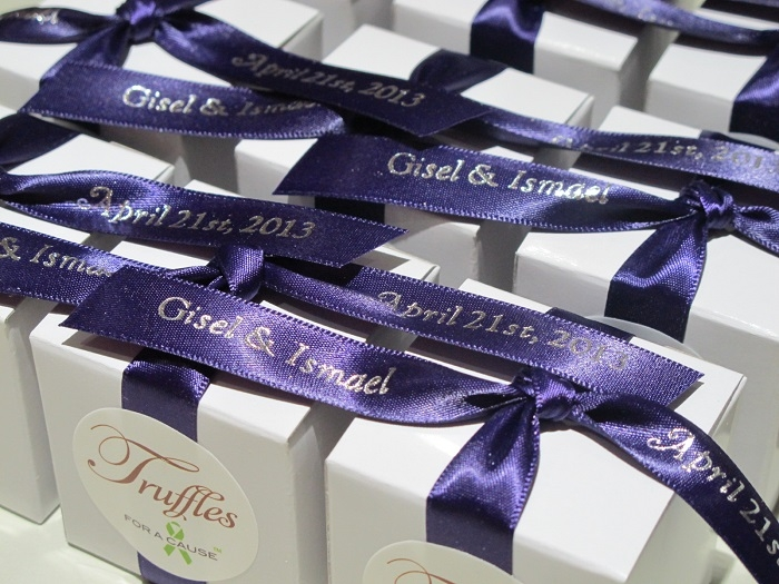 Grappa ribbons with gold print tied on white favor boxs with chocolate truffles inside.