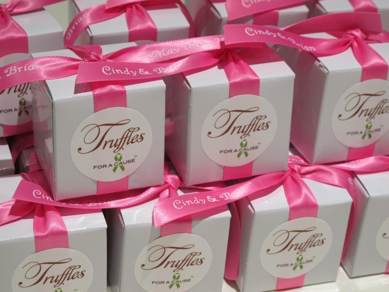 Hot Pink ribbons on white favor boxes with gold mini chocolate truffles inside.