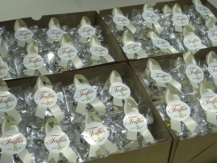Ivory ribbons tied on mini favors with silver chocolate truffles inside ready for shipping.