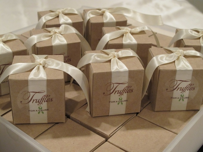 Ivory ribbons on natural kraft favor boxes with chocolate amaretto foil truffles inside.