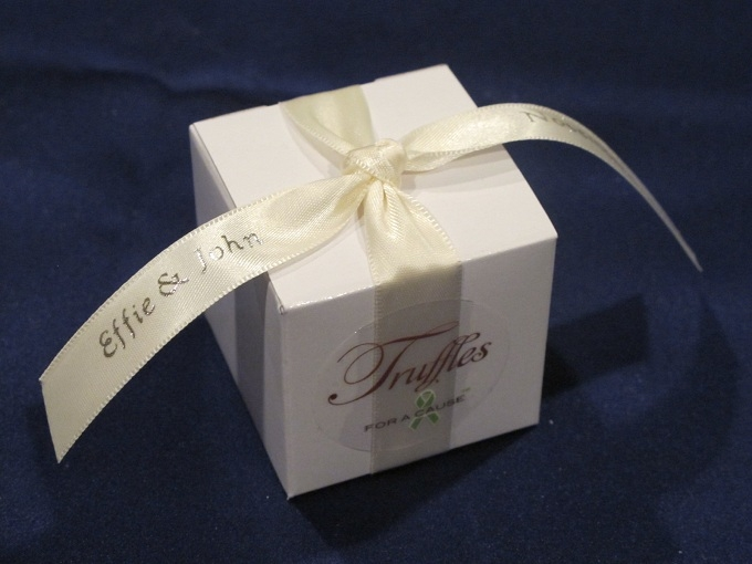 Ivory ribbon with gold print on white favor box with dark chocolate foil truffles inside.