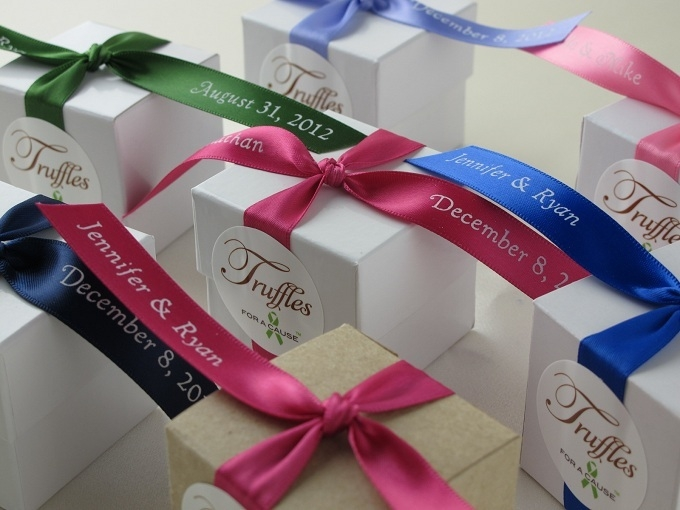 Close up of mixed colored ribbons on white favor boxes with chocolate mini truffles inside.