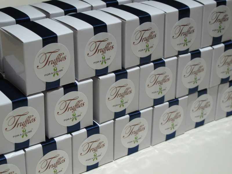 Navy ribbons on white  favor boxes in assembly group with chocolate mini truffles.