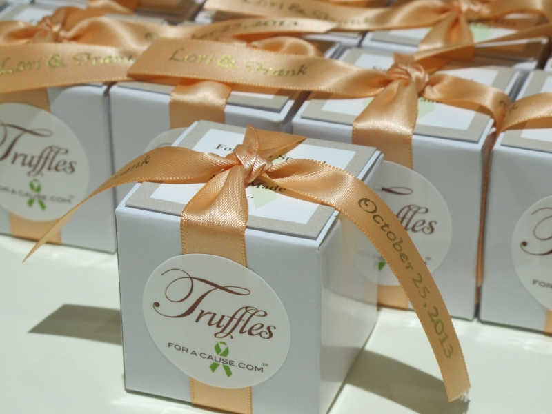 Peach ribbons on white favor boxes for an order with chocolate mini truffles inside.