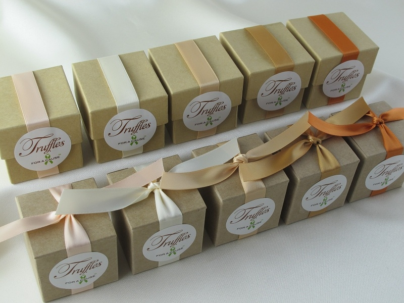 Peach, Ivory, Silk, Gold & Burnt Sienna ribbons on overhead kraft favor box display with various chocolate truffles inside.