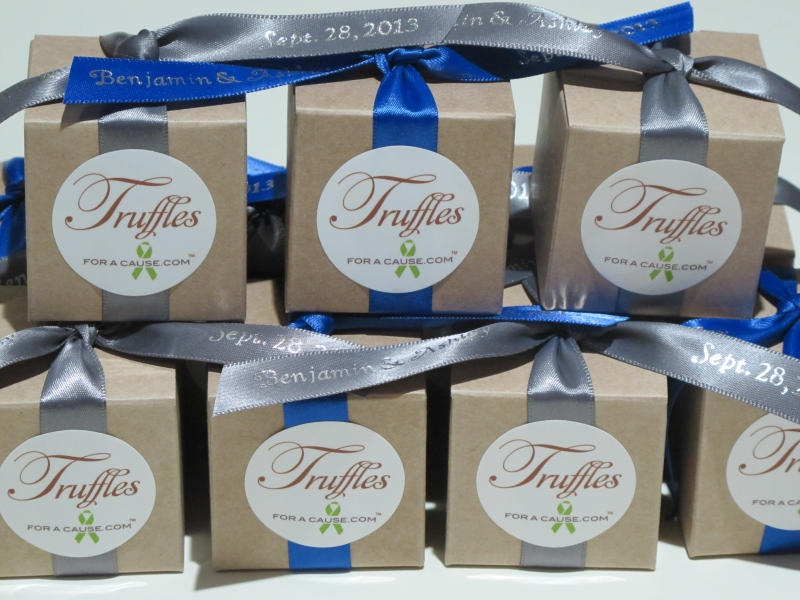 Pewter & royal blue ribbons on kraft favor boxes stacked for shipping with milk chocolate foil truffles inside.