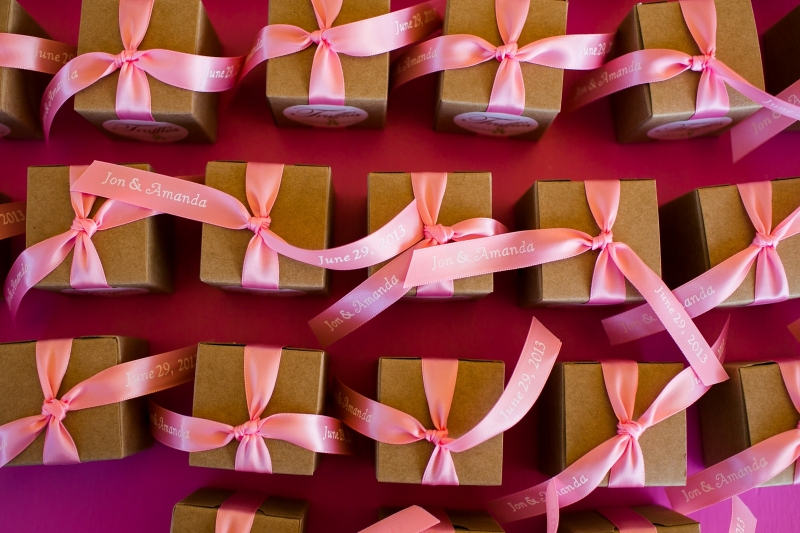 Over head view of pink ribbons on kraft favor table display containing chocolate mini truffles.