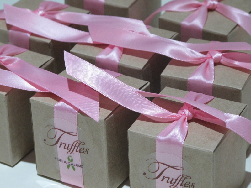 Pink ribbons on kraft favors for shiiping containing chocolate foil truffles.