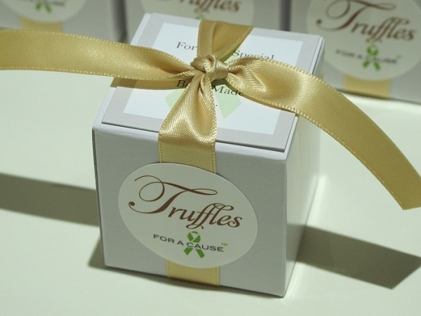 Raw Silk ribbon on white favor box (in front of), row of favors for shipping containing chocolate raspberry truffles.