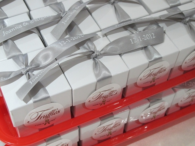 Silver ribbons on white favor boxes with milk chocolate foil truffles (inside), on  red assembly trays.