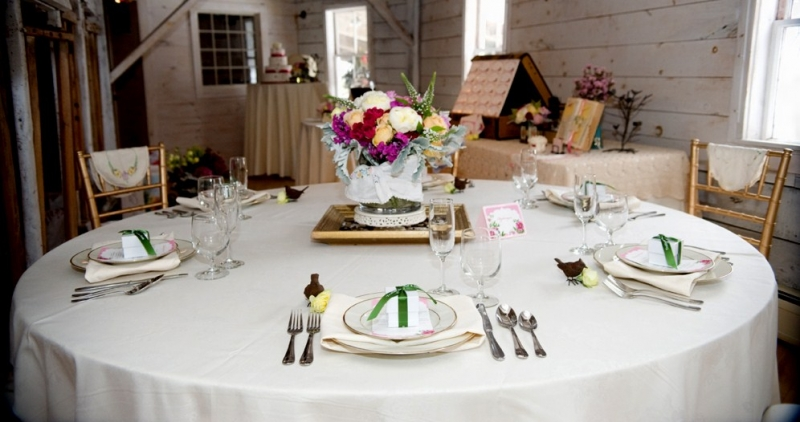 Round table setting -with leaf green ribbons on white favor boxes with chocolate raspberry & amaretto truffles.