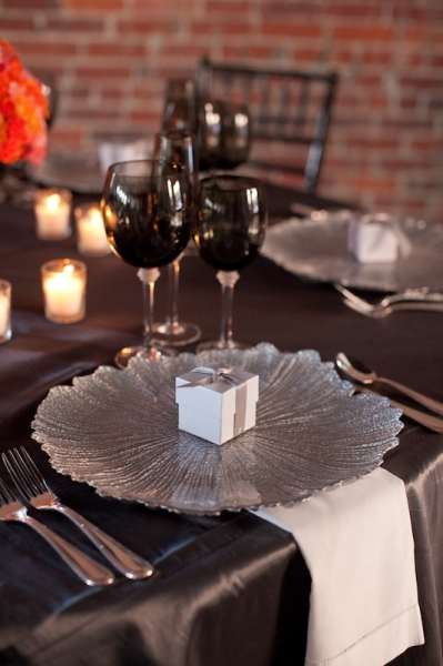 Table Setting with silver charger plate and silver ribbon on white dessert box with Irish cream jumbo chocolate truffle inside.